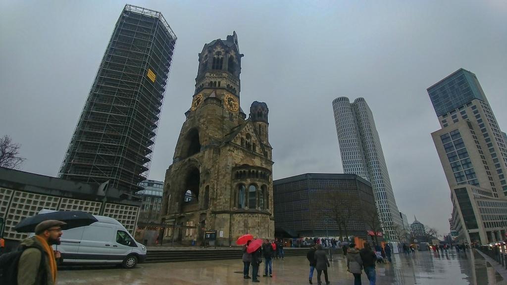 A do hotelu pak jdeme pěšky za drobného děštíku. Minuli jsme zajímavou ruinu Kaiser Wilhelm Gadachtnis Kirche s novým kostelem (ta nízká budova napravo)