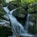 Sedm metrů vysoký vodopád s velkým balvanem zaklíněným uprostřed.