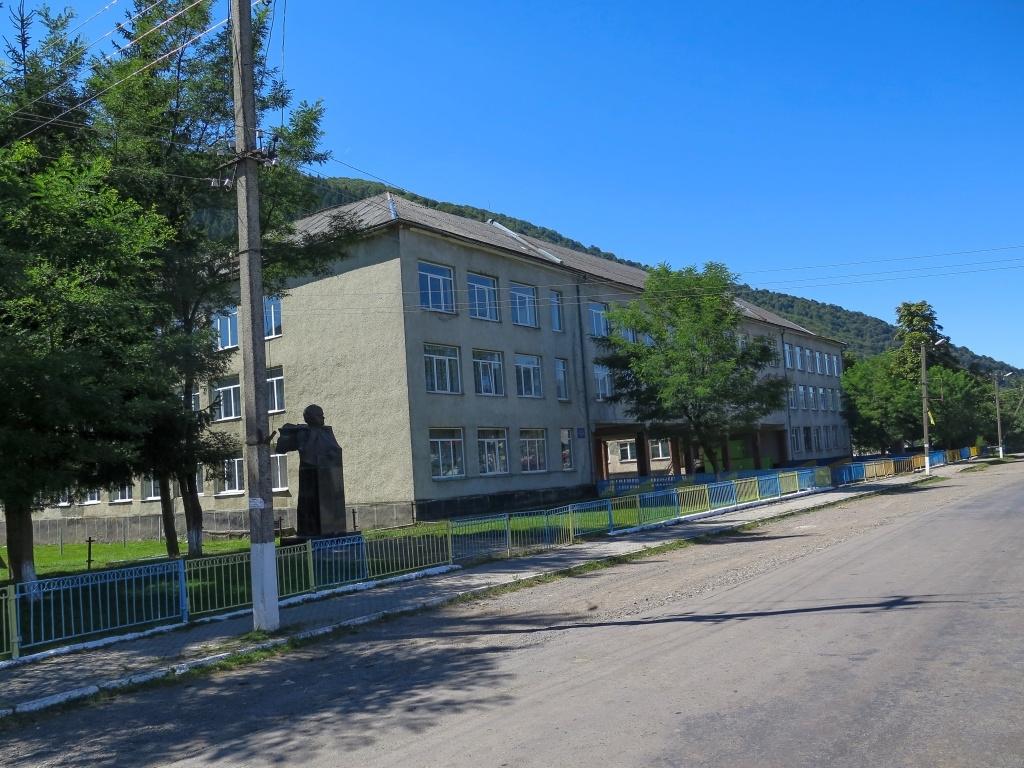 Přes nekonečnou vesnici... Domy se zahušťovaly a Luděk měl čím dál větší problém najít místo, kde přidřepnout ... a toužebně jsme vyhlíželi křižovatku a známou stavbu - školu Ivana Olbrachta