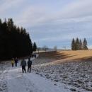 Ledva jsme se napojili na červenou značku, zase jsme se z ní odpojili a míříme úbočím kopce Adam, nejprve po cestě lesem, pak po pěšince přes louky, do Českých Petrovic.