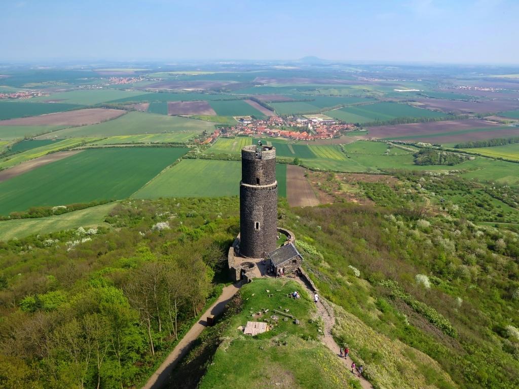 Pohled na spodní černou věž a obec Klapý. V dáli Říp.