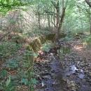 Zpevněný břeh potoka, kde vedla železnice