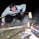 Luděk mohutným dechem rozdmýchává oheň.