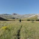 V obklopení vápencových hor pokračujeme širokým údolím. Travou vede sotva znatelná pěšinka vyšlapaná bůhví od koho.