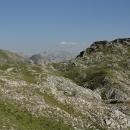 V proluce mezi vrcholky kopců se náhle objevují vysoké skalnaté hory – možná už jde o pohoří Volujak.