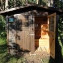 Dřevěná kadibudka u rastplacu (dokonale čistá, vybavená koberečkem, obrázkem na zdi, záclonkou – a několika ruličkami toaletním papíru, samozřejmě)