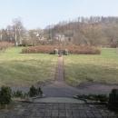 Pohled od pomníku směrem k přírodnímu labyrintu - nyní ještě bohužel zavřenému. Vzadu prosvítá zřícenina hradu.