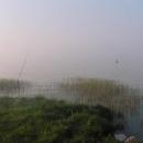 V ranní mlze nad jezerem se ztrácí loďka rybáře