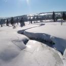 Meandry říčky Jizerky se rýsují v závějích sněhu