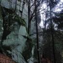 Zelená turistická značka vede přímo pod skalami,