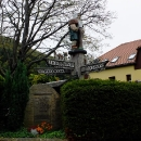 Sympatický rozcestník s vyřezávanými postavičkami u přechodu ve Waltersdorfu