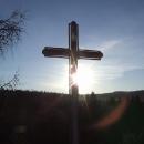 Na vrcholu skály stojí kříž