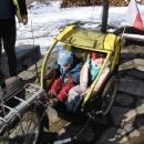 Děti navlečené v bundách jsou ve vozíku dost natěsno